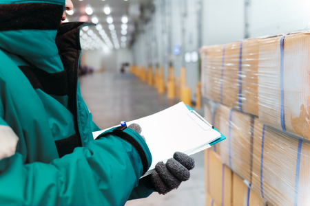 Hand of worker with clipboard checking goods in freezing room or warehouse. Export-Import Logistics system concept