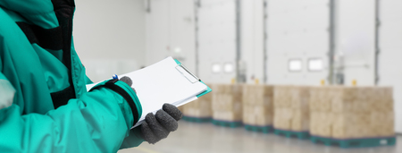 Hand of worker with clipboard checking goods in freezing room or warehouse. Export-Import Logistics system concept. Banners with copy space Stock fotó