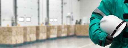 Safety Officer holding hardhat  for dangerous accident protection in warehouse during work. Cold room storage and freezing warehouse. Banners with copy space.