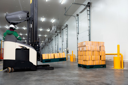 Worker Stand-on stacker truck used to lift and move the ready meals goods stock in cold room or freezer room.