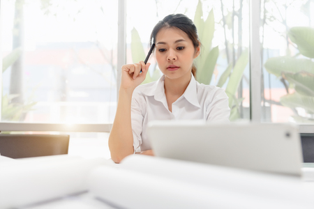 Asian female executive working thinking in her workplace with skillful