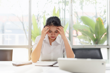 Tired Asian Business Woman with headache at office, visual migraine, retinal migraine, monocular migraine. Feeling sick at work. Thinking overworking in job concept 免版税图像