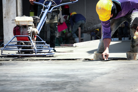 Construction labor, Plasterer concrete cement work. using a trowel to smooth or leveling concrete slab floor work step of the building construction. 免版税图像