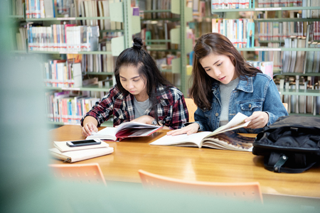 Two Asian female students open reading a textbook in the library room. Life of studying and friendship in International College/University. 免版税图像
