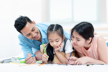 Asian people, Happy family in bedroom at home. Mother, Father and the children playing, Activities of family members are good family health of three people Education of kids, Health Insurance concept. 免版税图像