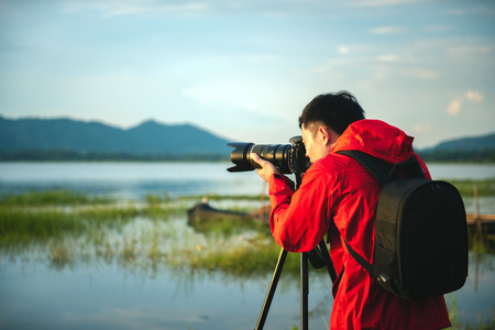 Travel photographer taking a photo with nature the lake in sunset with camera on tripod, Focusing attention nature mountain view and lake,  Natural photography relaxing concept. 免版税图像
