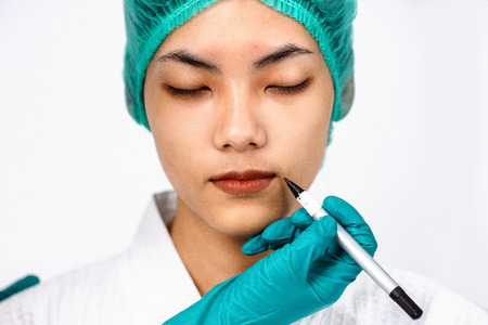 Beautiful portrait Asian woman tan skin in wearing medical hat while close eyes with Doctor's hand in glove prepare making lines marks on patients face before plastic surgery operation.