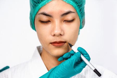 Schönes Porträt asiatische Frau bräunen die Haut beim Tragen eines medizinischen Hutes, während enge Augen mit der Hand des Arztes im Handschuh darauf vorbereitet sind, vor der Operation der plastischen Chirurgie Linien auf dem Gesicht des Patienten zu machen.