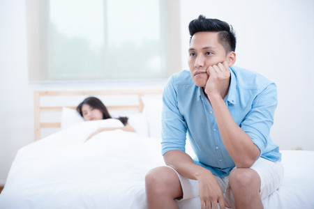 Husband unhappy and disappointed in the erectile dysfunction during while his wife sleeping on the bed. Sexual Problems in Men.