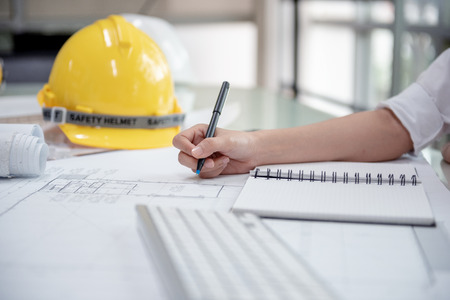 Engineer Designer Women. Drawing and Planning with Blueprint Architecture on Desk office. Drafting and Design Worksheets Before Startup Project Concept. 免版税图像