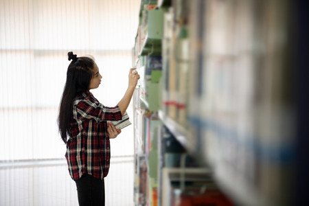 Asian Student searching for textbook in the bookshelf in the International College/University Library. Finding the correct answer to their question preparing for university examination. 免版税图像