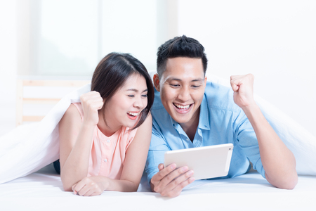 Asian young couple using a tablet while lying on the bed in the bedroom. High speed internet 5G service technology at home, Telecom networks designed concept.