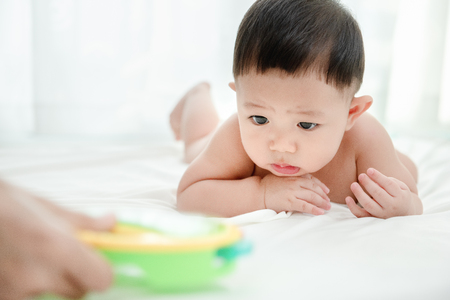 Asian baby boy doubts with colorful toys in mother hand. Baby skills develop concept.