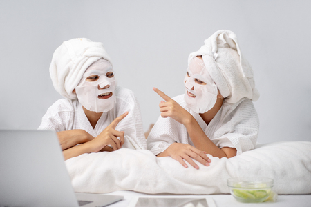 2 Young woman wrapped hair with towel while having fun with homemade facial mask. Beauty treatment process of aging for rejuvenation. Skin Restoration Whitening, Moisturizing, Brightening.