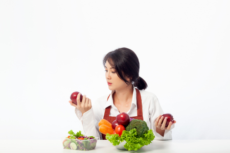 Asian young woman sits to holding apple with fresh fruit while Concerning Over Food Safety about Toxins in food. Antioxidant in meal, Risks in food safety, Clean eating food concept with copy space.