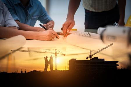 Burgerlijk ingenieur banen, dubbele blootstelling van projectmanagementteam en bouwplaats met torenkraanachtergrond, dag- en nachtploeg op het werkconcept van werknemers. Stockfoto