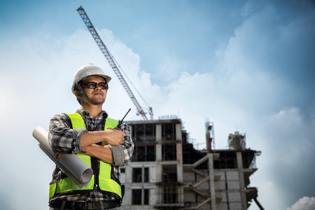 Engineers People holding blueprint in his hand at construction site or building site of highrise building 免版税图像