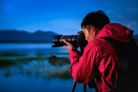 Travel photographer taking a photo with nature the lake in sunset to nightlife with camera on tripod, Focusing attention nature mountain view and lake,  Natural photography relaxing concept. 免版税图像