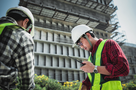Construction engineers discussion with consultant at construction site or building site of highrise building with blueprints
