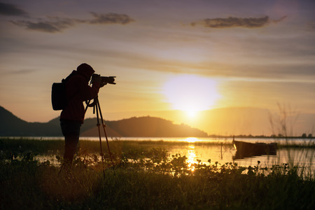 Travel photographer taking a photo with nature the lake in sunset to nightlife with camera on tripod, Focusing attention nature mountain view and lake,  Natural photography relaxing concept. Stok Fotoğraf
