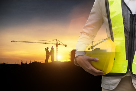 Civil Engineer and Safety officer, Double exposure of Safety officer holding hard hat and Construction Site with tower crane background.