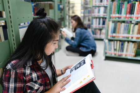 Asian female student sitting on floor in the library, Open and learning textbook from bookshelf in the International College/University Library.