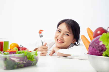 Asian young woman is happy holding a fork in hand with vegetables,  Healthy, Fresh food, Clean eating recipes to fuel body from the inside out concept. Banque d'images