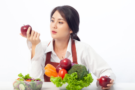 Asian young woman sits to holding apple with fresh fruit while Concerning Over Food Safety about Toxins in food. Antioxidant in meal, Risks in food safety, Clean eating food concept with copy space. 免版税图像 - 123736017