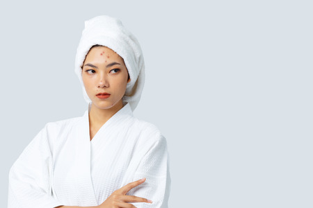 Portrait of Beautiful Asian woman tan skin wrapped hair with dissatisfied hopeless eyed, Dark spots skin, Skincare and clean concept, Beauty treatment process of aging for rejuvenation.