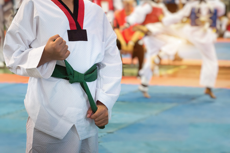 Taekwondo Kids action with uniform and green belt. Double exposure another player during the tournament taekwondo kids in stadiums