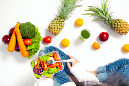 Top view of Young woman holding healthy vegetable salad and sitting with fresh fruit and Healthy diet, Concern Over Food Safety about Toxins in food. Antioxidant in meal, Clean eating food concept. Banque d'images