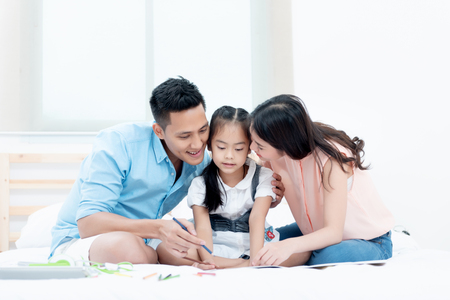 Asian people, Happy family in bedroom at home. Mother, Father and the children playing, Activities of family members are good family health of three people Education of kids, Health Insurance concept. Banque d'images