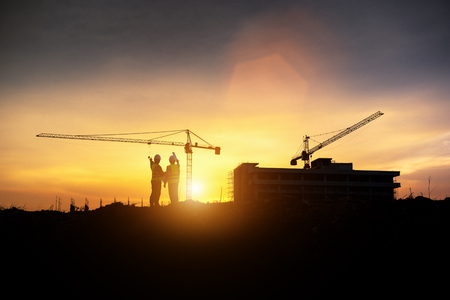 Silhouette engineer construction work control and tower crane background on natural sunset sky.,Heavy industry and building construction work concept