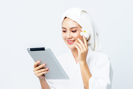 Portrait of beautiful woman holding and looking the tablet to watch skin care and clean concept, Technology access to Personalised Skincare.