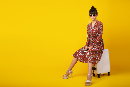 Asian young woman in vintage dress and wearing sunglasses sitting on white suitcase while her earphone on yellow background. Lifestyle, Fashion and travel concept. 免版税图像