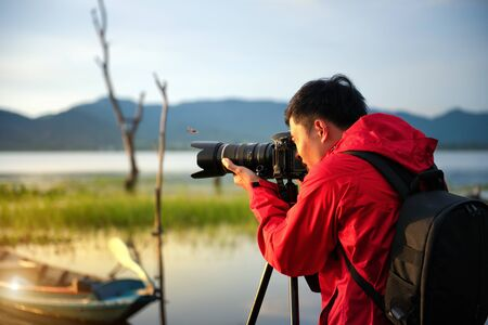 Travel photographer taking a photo with nature the lake in sunset with camera on tripod, Focusing attention nature mountain view and lake,  Natural photography relaxing concept. Banque d'images