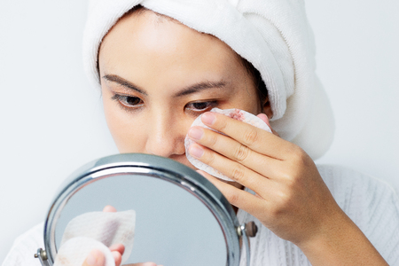 Beautiful skin care concept. Asian beautiful young woman focusing cleaning her face skin with Cotton Pad and looking the mirror.