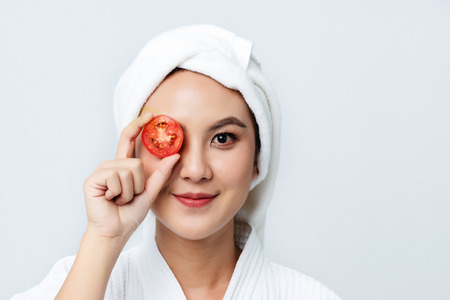 Natural homemade fresh cucumber facial eye pads facial masks. Asian woman holding tomato slices and smile relax with natural homemade. Banque d'images
