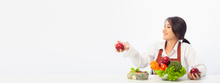 Asian young woman is happy holding fresh fruit apple with vegetables,  Healthy, Fresh food, Clean eating recipes to fuel body from the inside out concept with copy space banner.