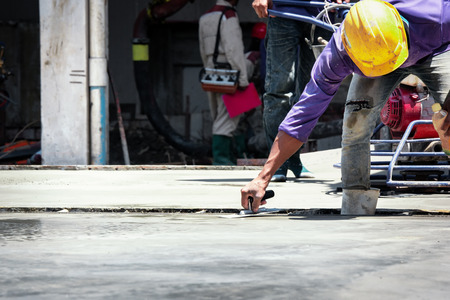 Construction labor, Plasterer concrete cement work. using a trowel to smooth or leveling concrete slab floor work step of the building construction. Banque d'images