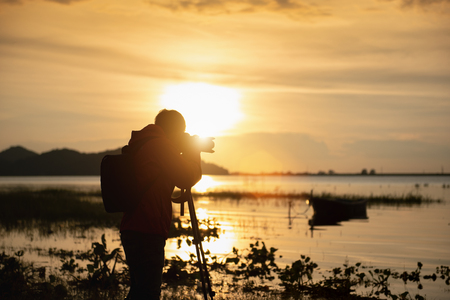 Travel photographer taking a photo with nature the lake in sunset to nightlife with camera on tripod, Focusing attention nature mountain view and lake,  Natural photography relaxing concept. Banque d'images