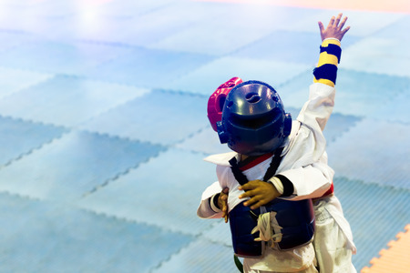 Signal from kids during Taekwondo fighting contest in Fighting on stage of Taekwondo tournament