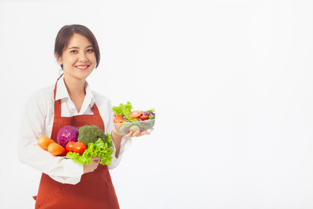 Asian young woman stands to hold vegetables with fresh fruit, Healthy diet. Antioxidant in meal, Risks in food safety, Clean eating food concept with copy space. 免版税图像