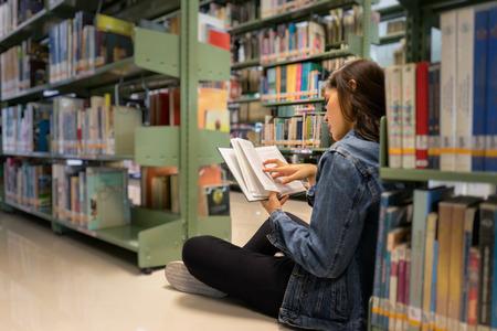 Estudiante asiática sentada en el piso de la biblioteca, libro de texto abierto y de aprendizaje de la estantería en la biblioteca de la universidad / colegio internacional Foto de archivo