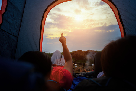 Young woman lying in a tent pointing sky view with sunlight in beautiful time of natural on mountains,  Camping with Sunset in base camp, One Activity Relaxing in summer 免版税图像