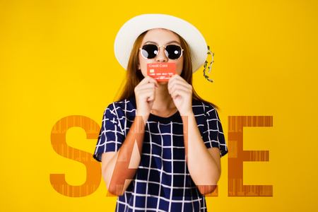 Blur image of Asian young woman portrait in sunglasses holding and kiss credit card with Sale text, Double Exposure, Shopping mid-year sale concept isolated on yellow background. 免版税图像