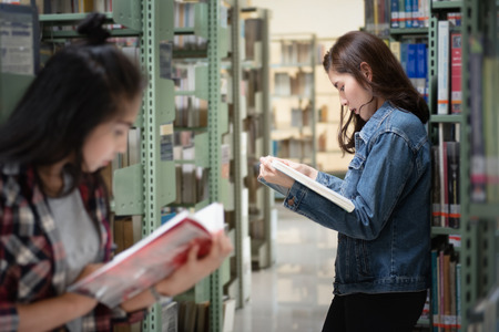 Asian female student open and learning textbook from bookshelf in the International College/University Library.