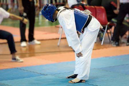 Taekwondo Kids be tired in Moment of during the tournament taekwondo kids in the stadiums. Athlete to strike an opponent during the tournament taekwondo kids. Stok Fotoğraf