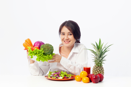 Asian young woman holding salad vegetables with fresh fruit and Healthy diet on the table.  Antioxidant in meal, Risks in food safety, Clean eating food concept with copy space.