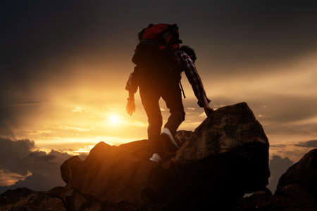 Hikers climbing up mountain cliff in sunset. Concept of limits of life and Hiking success full.